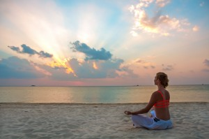Young woman meditation on the beach at the sunset ** Note: Soft Focus at 100%, best at smaller sizes